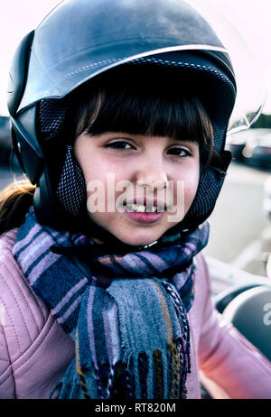 Portrait of little girl with tooth gap wearing helmet on motorcycle - Stock Photo