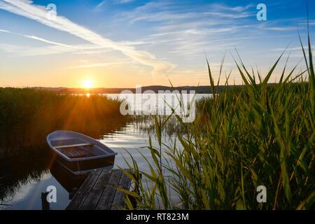 Germany, Mecklenburg-Western Pomerania, Ruegen, Sellin, empty rowing boat near jetty at sunset