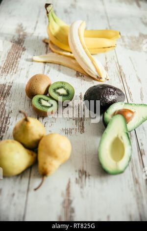 Pears, peeled and whole banana, sliced and whole avocado and kiwi - Stock Photo