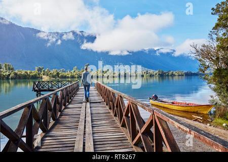 Chile, Chaiten, Lago Rosselot, woman walking on jetty