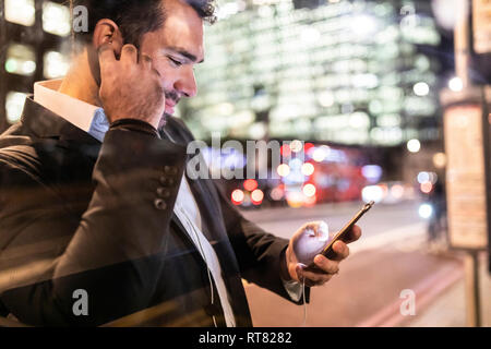 UK, London, businessman on the go checking his phone while commuting by night - Stock Photo