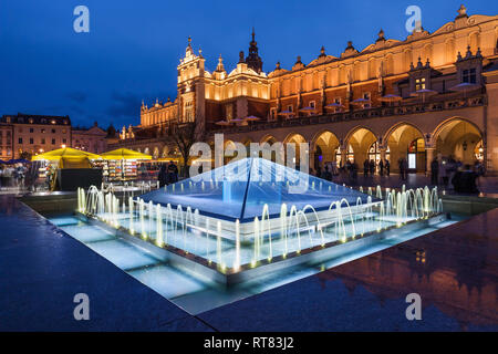 Poland, Krakow, Main Square in Old Town at night, illuminated fountain and Cloth Hall - Stock Photo