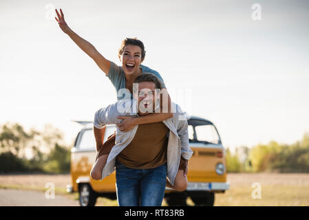 Happy couple doing a road trip with a camper, pretending to fly on the road - Stock Photo
