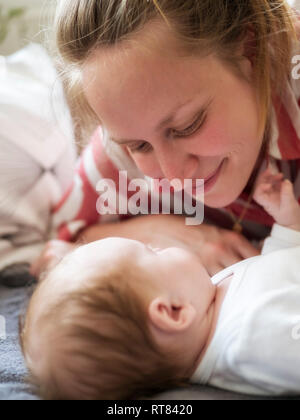 Smiling mother atching her baby daughter - Stock Photo