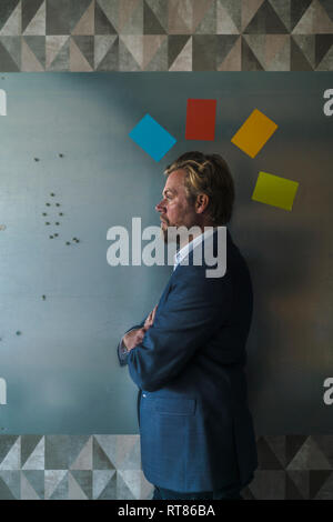 Businessman standing in front of magnet wall with mohican from colorful sticky notes - Stock Photo