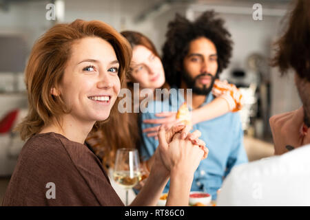 Friends having fun at a dinner party, enjoying eating together - Stock Photo