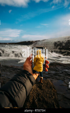 3D montage of man taking smartphone picture of Iceland's landscape and woman wearing yellow raincoat - Stock Photo