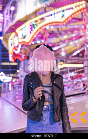 Teenage girl hiding her face behind pink candyfloss at fair - Stock Photo