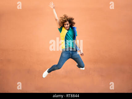 Happy young man with curly hair wearing waistcoat jumping in the air - Stock Photo