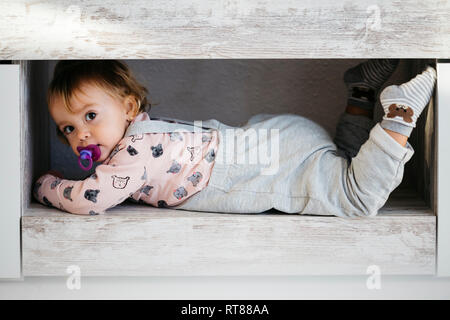Portrait of baby girl with pacifier hiding at home - Stock Photo