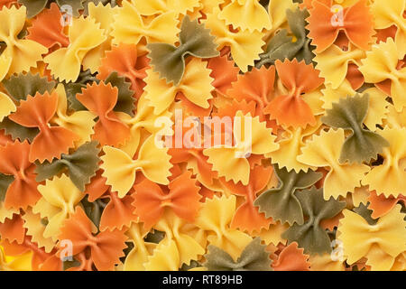 Raw farfalle pasta stack top view isolated on yellow background a lot of dry pieces - Stock Photo