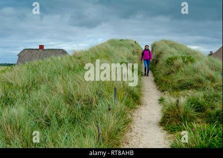 Denmark, Jutland, Henne Strand, woman walking in dunes - Stock Photo