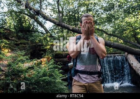 Young man with backpack refreshing at water in a forest - Stock Photo