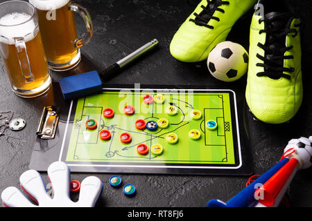 Photo of two mugs of foam beer, table football, ball, football boots, pipe, rattle toy - Stock Photo