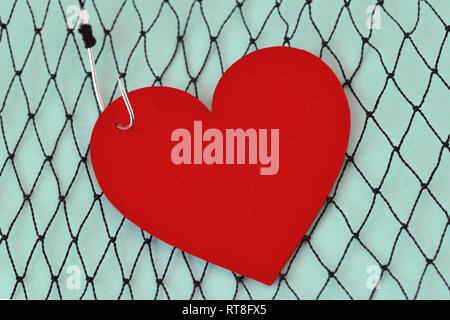 Heart on fish hook on fishing net - Love concept - Stock Photo