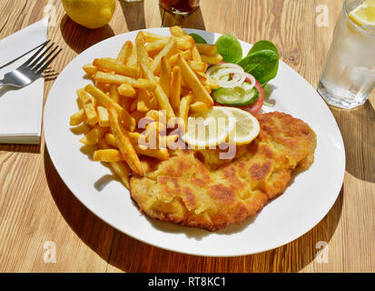 Schnitzel with French Fries on wooden Background - Stock Photo