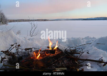 A fire is burning in the snow at the shore of an ice-covered lake as the sun is setting on a cold winter day. - Stock Photo