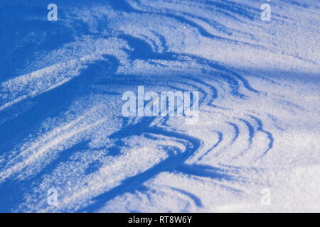 The wind has formed patterns in the snow covering a frozen lake. - Stock Photo