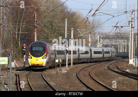 Class 390 Pendolino electric multiple unit train in Virgin West Coast flowing silk livery leaving Lancaster railway station, WCML, 25th February 2019. - Stock Photo