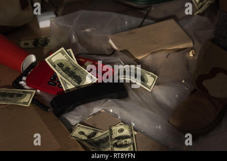 cropped view of male leg in boot near vintage phone, book and money scattered on floor - Stock Photo