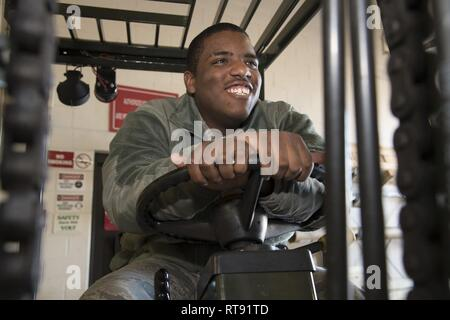 Airman Anthony Lemarc Cole Jr., a traffic management specialist, 108th Logistics Readiness Squadron, poses for a photo while seated on a forklift at Joint Base McGuire-Dix-Lakehurst, N.J., Feb. 4, 2019. Cole said what he enjoys most about traffic management is that he is hands-on at all times. - Stock Photo
