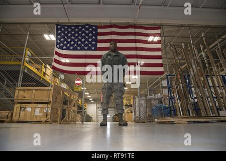 Airman Anthony Lemarc Cole Jr., a traffic management specialist, 108th Logistics Readiness Squadron, poses for a photo in the LRS supply warehouse at Joint Base McGuire-Dix-Lakehurst, N.J., Feb. 4, 2019. As a TMO specialist, Cole's duties include packaging, classifying, and arranging personal property and cargo for shipment or storage across the globe via air, ground, rail & vessel transportation. - Stock Photo
