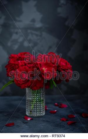 Shrub red roses in vintage glass vase on dark background. Copy space. - Stock Photo