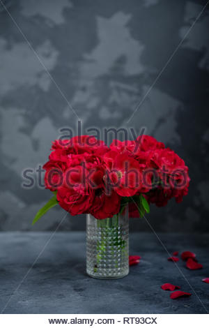 Bouquet of red roses in vase on concrete table and dark background. Copy space. - Stock Photo