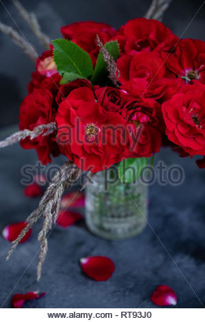 Rustic bouquet of red roses and feather grass in glass vase on dark background. View from the top. Close up. - Stock Photo