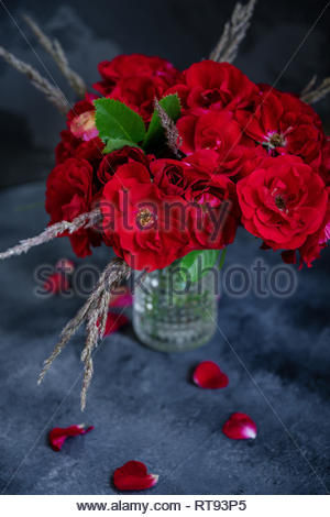 Original bouquet with shrub red roses in textured vase on dark grey concrete background. View from the top. - Stock Photo