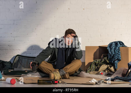 depressed homeless man holding paper cup while sitting on cardboard surrounded by rubbish - Stock Photo