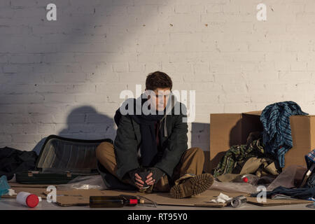 depressed homeless man sitting on cardboard and holding paper cup - Stock Photo