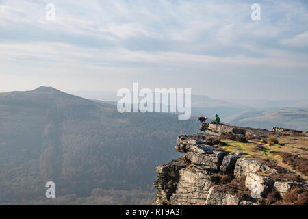 Rock climbers on Bamford Edge in the Peak District looking out over the landscape towards Lose Hill and Mam Tor in the distance on a Winter's day - Stock Photo