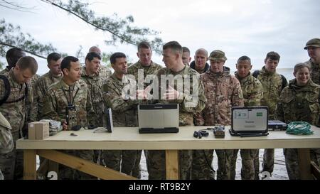 Service members from the Joint Communications Support Element and the British Army's 30th Signal Regiment gather around U.S. Army Staff Sgt. Kevin Shells (center), a JCSE systems team chief, at Beer Can Island, Fla. Jan. 30, 2019, as he demonstrates how to set up and utilize communications equipment in a deployed environment with no power source. As part of the Cobb Ring exercise, the two nations trained together to demonstrate capabilities with coalition partners and strengthen relationships. - Stock Photo