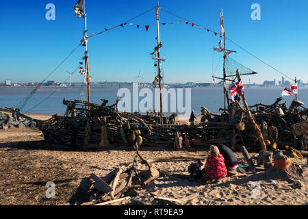 Children play on The Black Pearl Pirate Ship, a community art installation on the beach made from driftwood at New Brighton Merseyside UK. - Stock Photo
