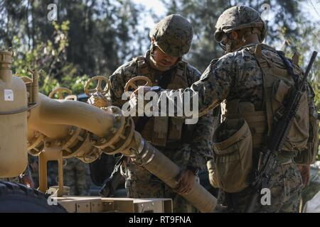 Cpl. Angel A. Pena, left, and Pfc. Gilberto Loza-Machado, right, attach a fuel hose to a fuel pump on Jan. 28, 2019 at Central Training Area, Camp Hansen, Okinawa, Japan. Marines with 2nd Platoon, Bulk Fuel Company, 9th Engineer Support Battalion, 3rd Marine Logistics Group, assembled several fuel sites across the CTA to enhance their training and readiness within a harsh environment. The Marines set up and maintained their bulk fuel equipment during a week-long training evolution. Pena, a native of Las Vegas, Nevada, is a bulk fuel specialist with 2nd Plt., Bulk Fuel Co., 9th ESB, 3rd MLG. Lo - Stock Photo