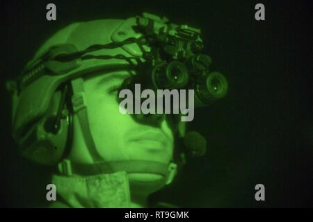 (Jan. 29, 2019)  U.S. Marine Corps Sgt. Xavien Harvey, a Marine with the 22nd Marine Expeditionary Unit, scans the flight deck with PVS-31 Night vision optics during a visit, board, search and seizure  night training event on the Whidbey Island-class dock landing ship USS Fort McHenry (LSD 43). The Maritime Raid Force continually trains with night optic devices during VBSS scenarios in order to maintain proficiency. Marines and Sailors with the 22nd MEU and Kearsarge Amphibious Ready Group are currently deployed to the U.S. 5th Fleet area of operations in support of naval operations to ensure  - Stock Photo