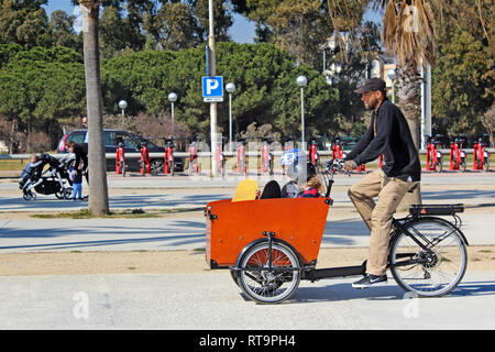 Father cycling with his children in a bicycle trailer, Mar Bella beach, Poblenou, Barcelona, Spain - Stock Photo