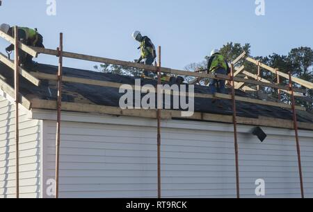 Repairmen with Headco Industries remove damaged singles while repairing the roof of a home located in Paradise Point housing on Marine Corps Base Camp Lejeune, North Carolina, February 1, 2019. Repairs are being made to homes and facilities on MCB Camp Lejeune and Marine Corps Air Station New River that sustained damage as a result of Hurricane Florence in September 2018. - Stock Photo
