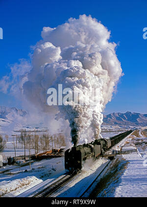 Two class QJ 2-10-2 steam locomotives hauling a heavy freight train in winter at Jingpeng, Inner Mongolia, China in January 2005 - Stock Photo