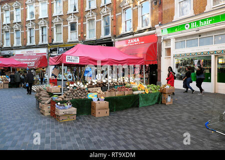 Vegetable stall & row traditional terraced housing above shops on Electric Avenue street market in Brixton South London SW9 England UK KATHY DEWITT - Stock Photo