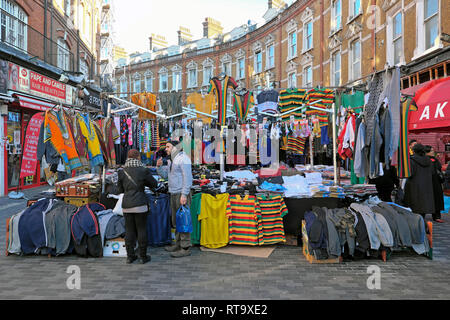 A market trader man selling mens clothing and football shirts in Brixton street market Electric Avenue Brixton South London England UK   KATHY DEWITT - Stock Photo
