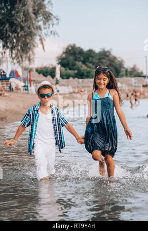 Cute little boy and girl running through the water at the beach - Image. The focus is on the water - Stock Photo