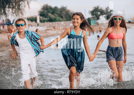 Happy children running through the water at the beach - Image - Stock Photo