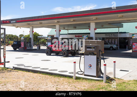 Total petrol or gasoline station forecourt with cars busy filling up with fuel and unattended fuel pump at Melkbosstrand, West Coast, South Africa - Stock Photo