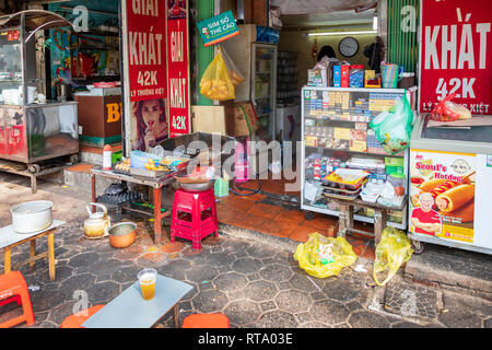 Exterior of a shop with a small cooking stove with food for sale at a street kitchen , Hanoi Old Quarter, Hanoi, Vietnam, Asia - Stock Photo