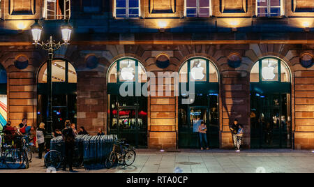 STRASBOURG, FRANCE - SEPT 18, 2014: Night view of Apple Store facade building with impatient customers waiting in queue and tents for the upcoming Apple iPhone, Apple Watch and other new products - Stock Photo