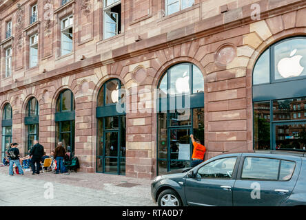 STRASBOURG, FRANCE - SEP 9, 2014: Customers waiting outside Apple Store prior the launch day of the newest iPhone Apple Watch iPad iMac computers - large Apple Store facade with computer Apple logotype - Stock Photo