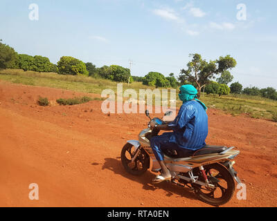 BAMAKO, MALI - DEC 19, 2016: African paysage with Touareg on his KTM bike driving fast ont the red african soil  - Stock Photo