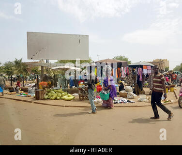 BAMAKO, MALI - DEC 19, 2016: View from the humanitarian vehicle of a generic urban market shopping street of the Bamako with people selling on the streets diverse object and vegetables - Stock Photo